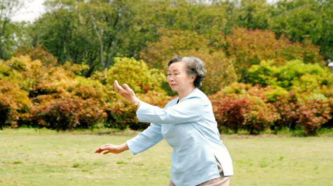 old woman practicing tai chi-compressed