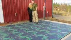 Scott and Julie Bradshaw stand on a prototype for a Solar Roadway parking lot. The prototype is largely finished, aside from mounting holes, mastic between panels, and software for LED patterns that still need to be added.